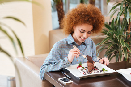 Cute curly young woman eating dessert in cafe