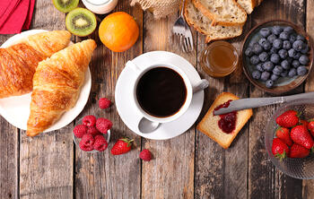 croissants, cup of coffee, fruits, breakfast restaurant